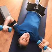 man doing sports with dumbbells lying on mat top view