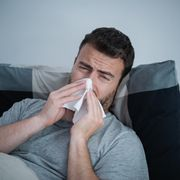 man in bed sneezing nose and feeling sick
