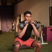man in gym using kettle bells