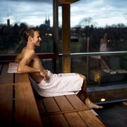 man sitting in a sauna with woman reflected in panoramic window