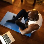 man watching gym class on laptop and doing exercises at home