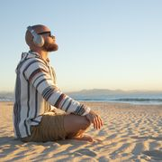 man with headphones sitting at the beach