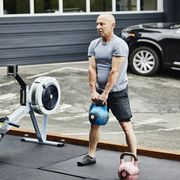 mature man doing kettlebell squats during workout at outdoor gym