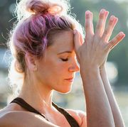 woman with pink hair and wearing workout clothes doing meditation outside