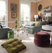 living room, orange walls, art on walls, maroon ottoman, green cushions