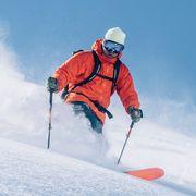 man in orange jackets skiing