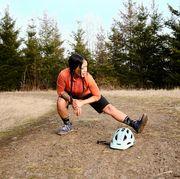 a mountain biker stretching her leg