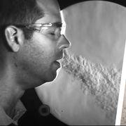 man exhaling vapor next to petri dish of coronavirus