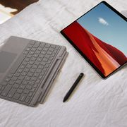 microsoft surface keyboard and pen on bed
