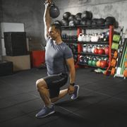 mid adult man practicing walking lunge with kettlebell during cross training in the gym