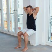 middleaged man exercising wall sit for legs