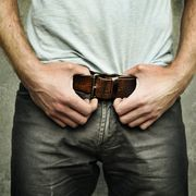 midsection of man holding his belt against wall