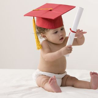 mixed race baby girl wearing mortarboard and holding a diploma