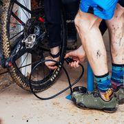 a mountain biker pumping air into a rear tire