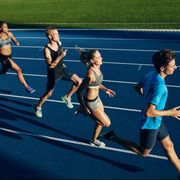 Multiracial athletes practicing running on racetrack