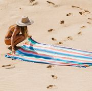 woman in straw hat laying down oversized striped towel on beach