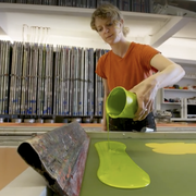woman pouring neon green paint onto a screen to make wallpaper