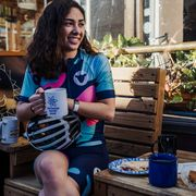 female cyclist eating outside a cafe