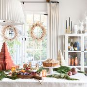 christmas buffet table with metallic decor and mini paper trees