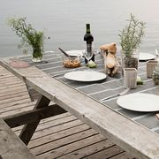 dinner set on wooden picnic table next to lake