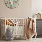 pillows and toy in white wooden crib with pastel pink blanket in bright nursery