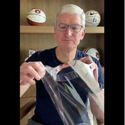 Tim cook holding an Apple face shield