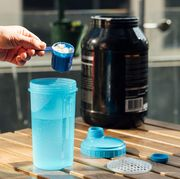 person mixing protein into shaker bottle