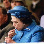 Queen Elizabeth II putting on lipstick