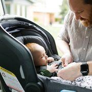 dad buckling baby into rear facing car seat