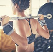 Rear view of woman exercising with barbell in gym