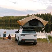 front runner roof top tent on top of car next to lake