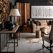 black painted walls, black crown moulding, brown sofa couch, brown trunk, circular wooden coffee tables,