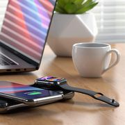 apple watch charging with iphone on power bank next to laptop