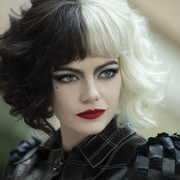 emma stone, a white actress, wears a black and white wig and red lipstick in a still from cruella