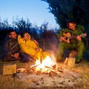 people wearing  selk'bag wearable sleeping bags around a campfire