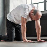senior bald yogi men practices yoga asana marjariasana or catcow pose