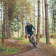 senior male on bike trail in forest