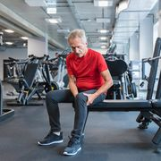 senior man suffering from knee pain at gym