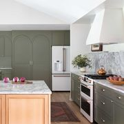 kitchen, olive green cabinets, wooden island with marble countertop, white oven, white range hood