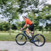 side view asian chinese female professional cyclist athlete sportsman sprinting cycling in public park