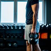 side view of a young man cross training with kettle bell