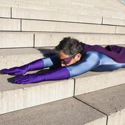 side view of man dressed as superhero lying on steps