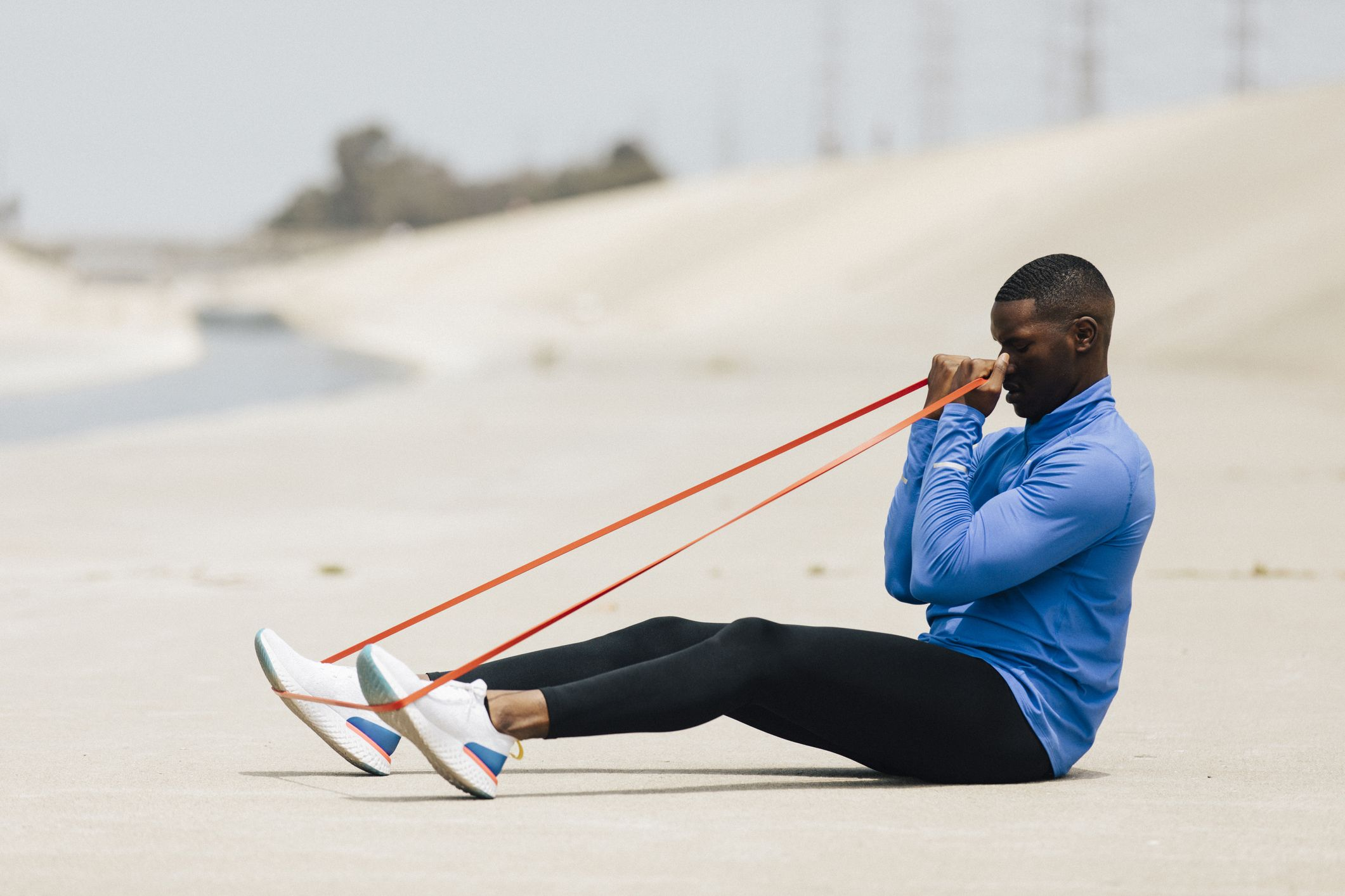 Side view of man stretching resistance band while sitting on land during sunny day