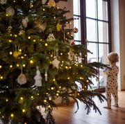 A small girl in sleepsuit indoors at Christmas time, looking out through window.