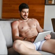 smiling male in underwear relaxing at home and using digital tablet