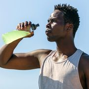 athlete drinking sports drink in water bottle