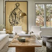 living room, wooden coffee table, white lounge chairs, white sofa couch, black and white ottomans, large artwork