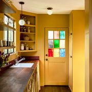yellow kitchen with stained glass window