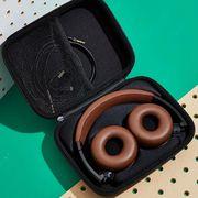 status audio headphones against pegboard and in case