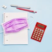 still life of a surgical mask, note pad, calculator and pens on blue background, wearing protective face mask at school
